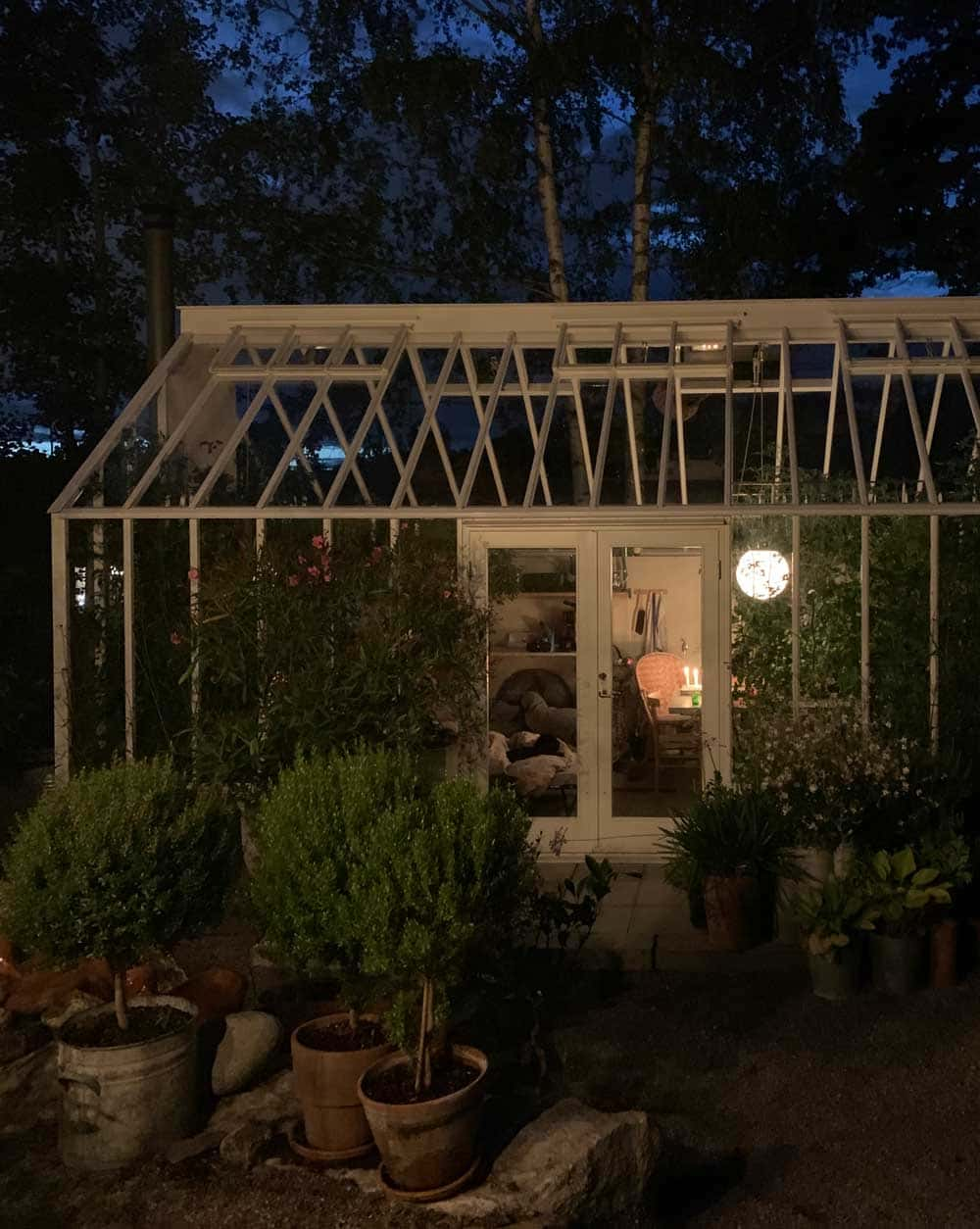 Tända ljus och klotlampa i växthus.