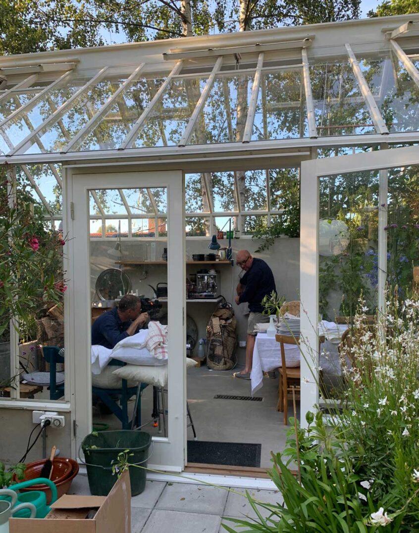 Två män med kamera i växthus.