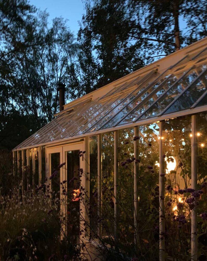 Upplyst växthus i skymning.