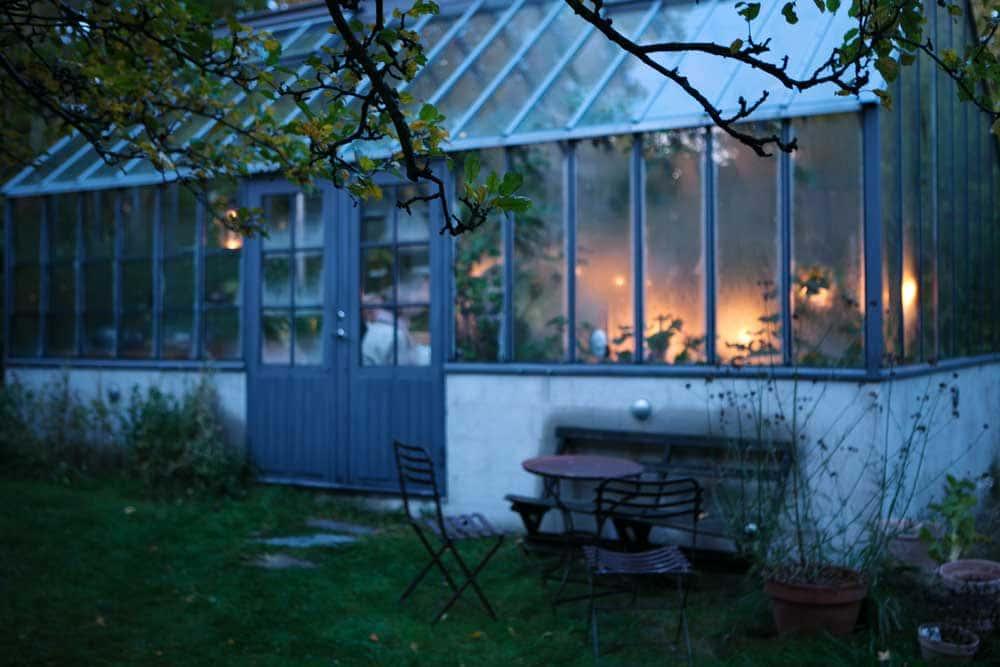 Grått växthus i skymning.