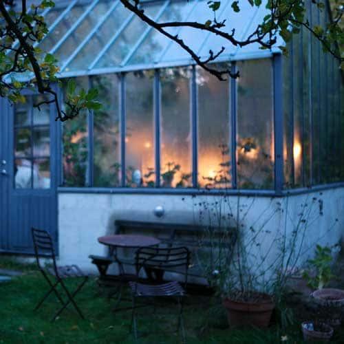 Ett grått växthus i skymningsljus.
