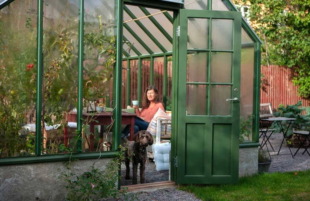 Dam med hund i växthus.