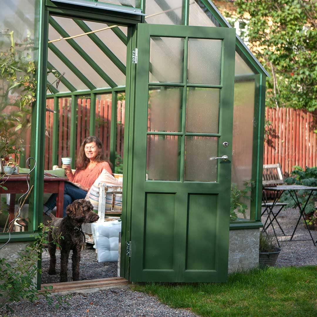 En kvinna som tittar på en hund i ett växthus.