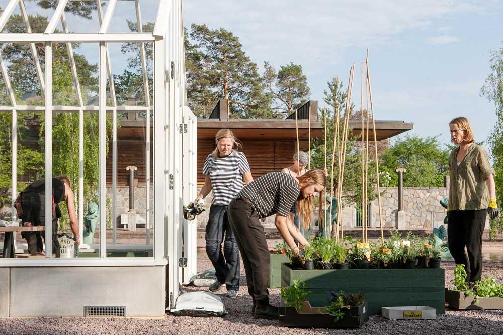 tre kvinnor vid växthus.