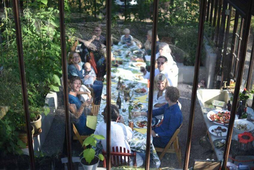 Människor runt ett middagsbord i växthus.