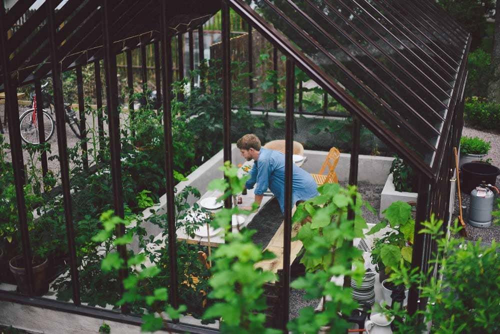 Man dukar i brunt växthus.