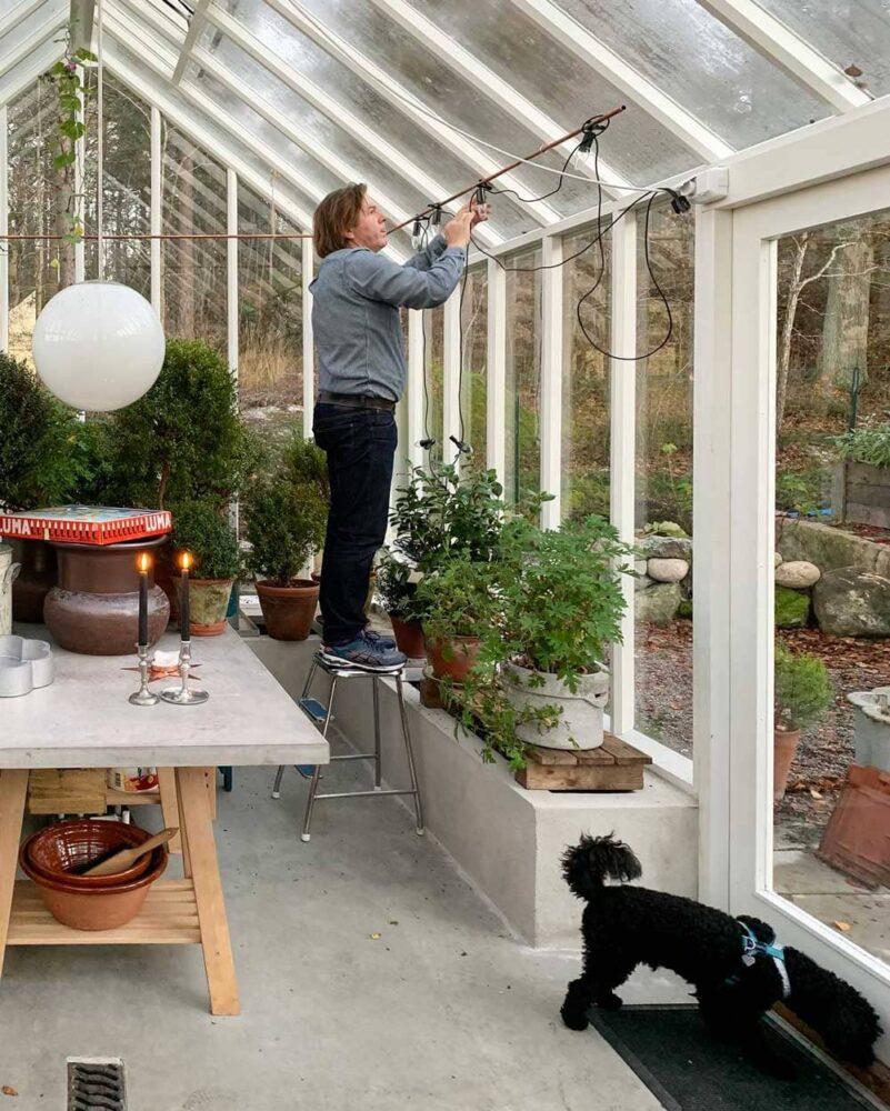 Man hänger julgransbelsyning på kopparrör.