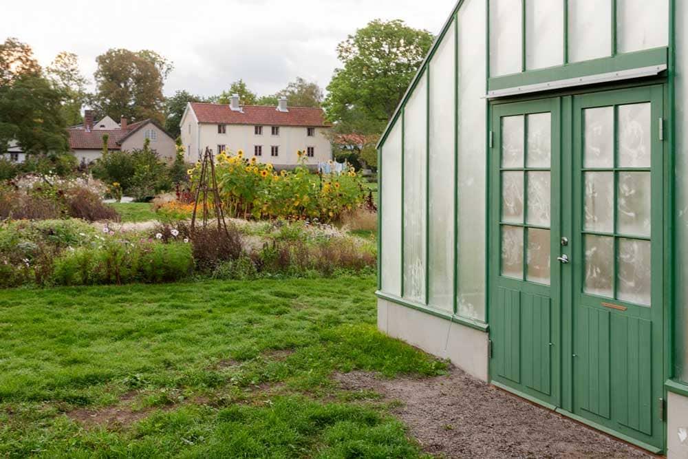 Vy över lummig park med växthus i förgrund.