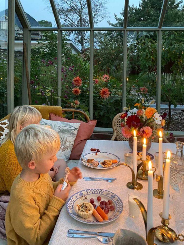 Två barn över en måltid i växthus.