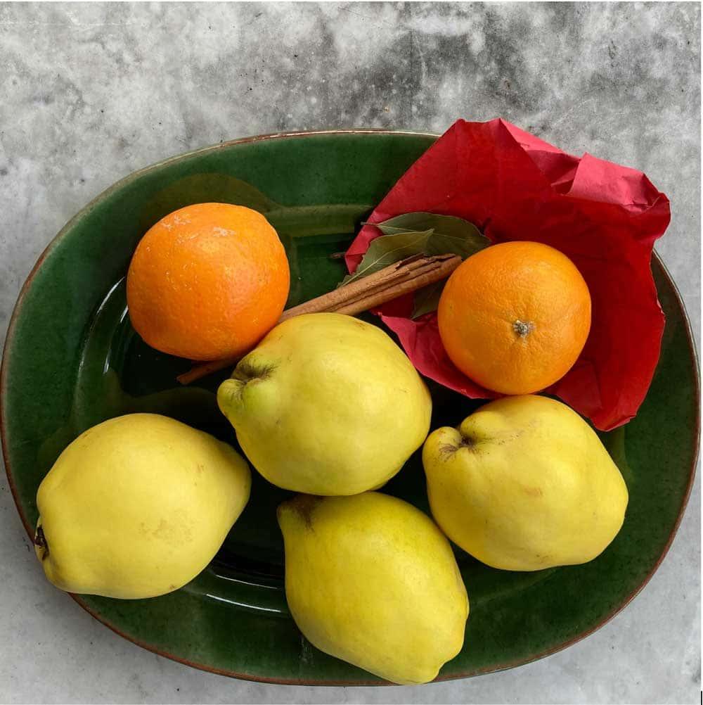Kvitten och apelsiner på grönt fat