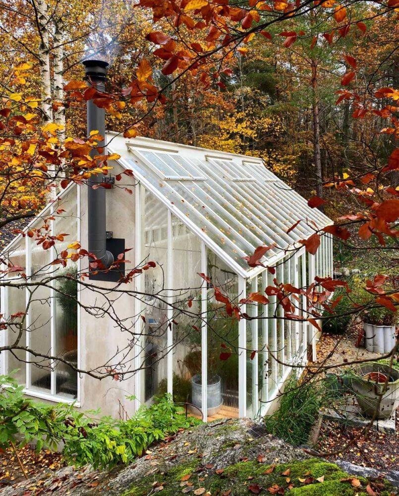 Vitt växthus i nedanför sluttning.