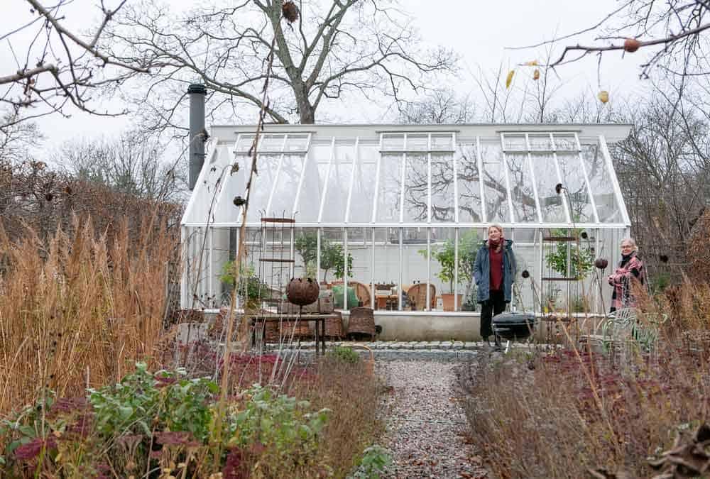 Två kvinnor i trädgården framför ett växthus.