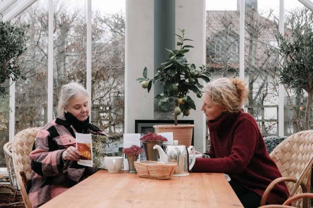 Två sittande kvinnor vid träbord.