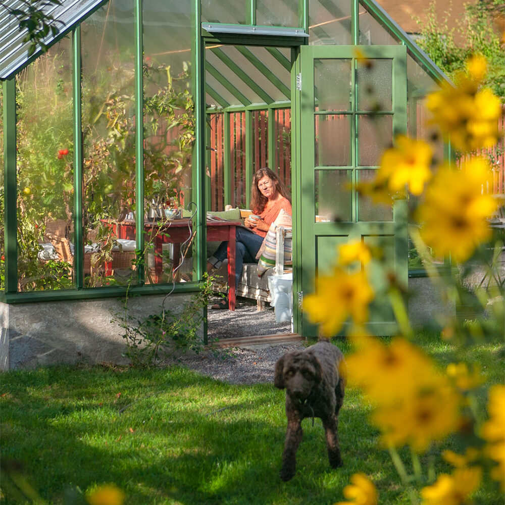 Kvinna i grönt växthus och hund.