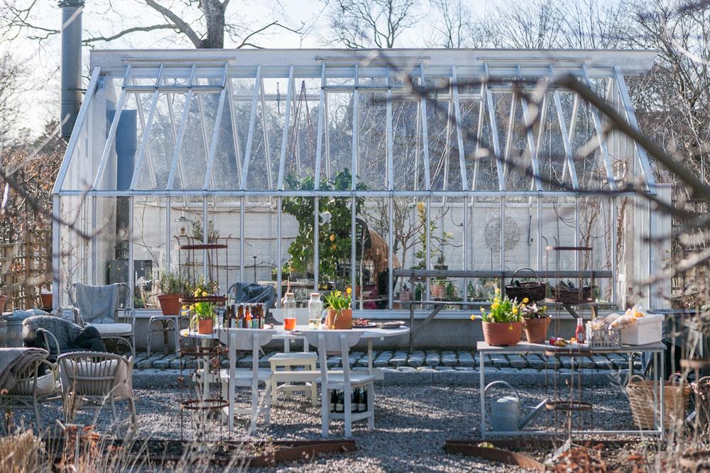 vitt växthus i vårljus.