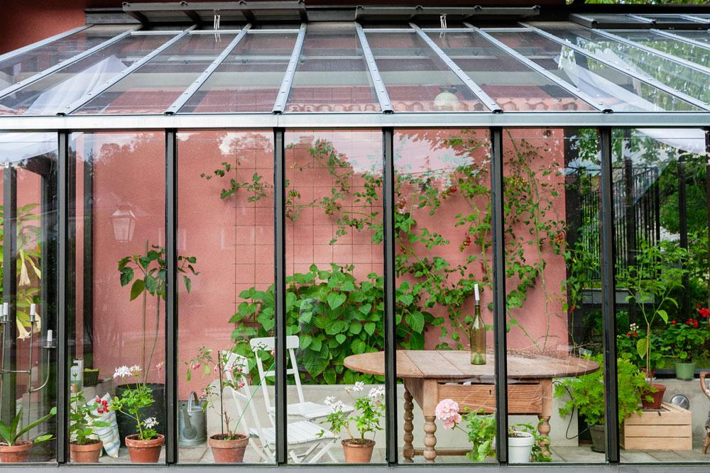 ett svart växthus monterat mot husvägg.