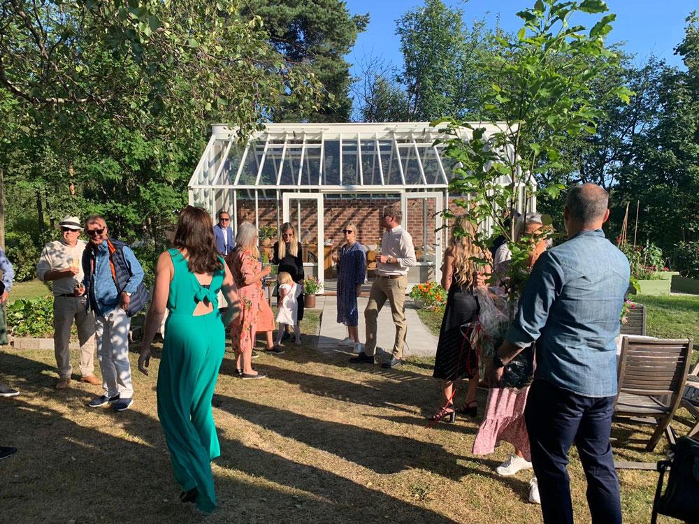 Födelsedagsfirande människor vid växthus.